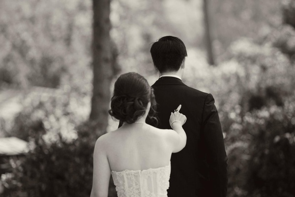 Black and white photo of bride poking groom's back