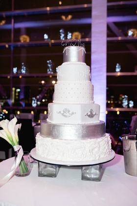 Wedding cake on legs with white silver and cream decorations different designs on each layer