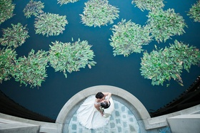bird's eye view of bride and groom kissing next to pond with greenery skirball cultural center
