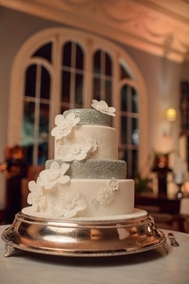 Four layer wedding cake with alternating white and silver tiers