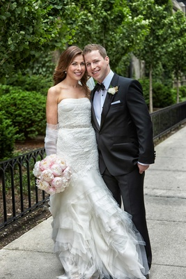 Bride strapless Vera Wang wedding dress with ruffle skirt, groom in tuxedo, and pink peony bouquet