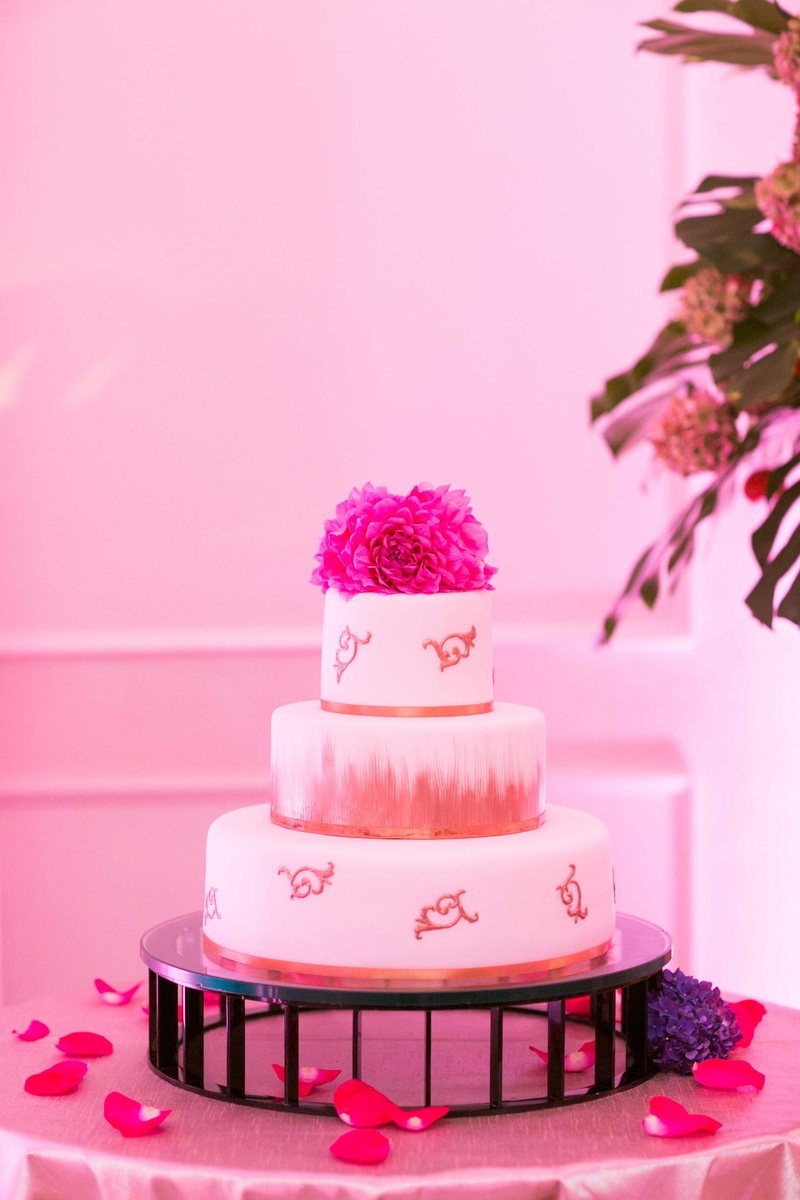 White fondant wedding cake with gold paintbrush stroke details and fresh flower cake topper in pink