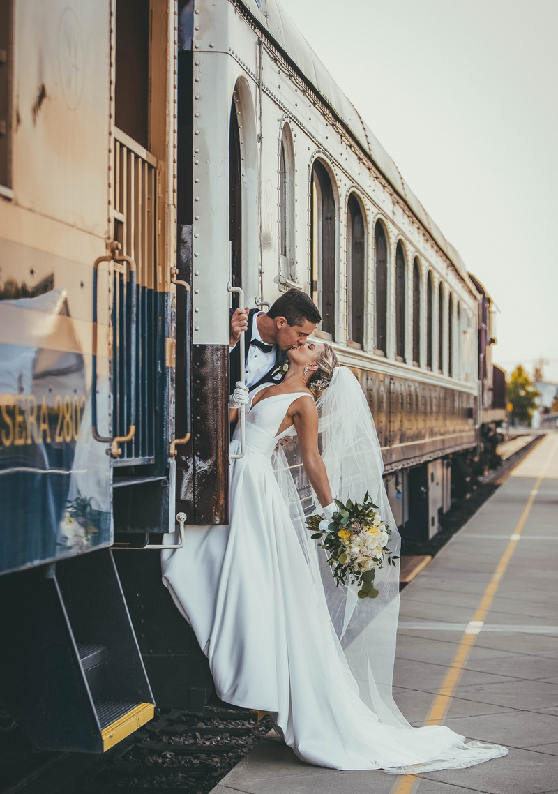 bride in stella york wedding dress kissing groom as they lean out of a train