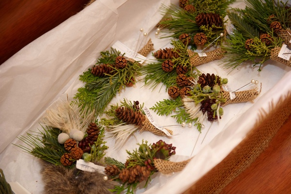 Christmas tree and pinecone boutonnieres wrapped with burlap