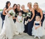 Bride in Maggie Sottero wedding dress with navy blue bridesmaids and two flower girls