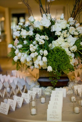 Table with escort cards and tulip and rose arrangement