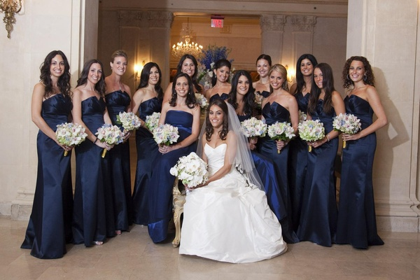 Bride in a Romona Keveza dress and veil with bridesmaids in long dark blue Badgley Mischka dresses