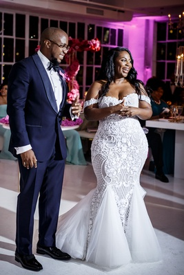Bride in mermaid dress and groom in tuxedo african american couple off shoulder gown reception