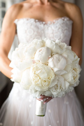 Bride in strapless wedding dress and white manicure nails holding white bouquet of peony flowers