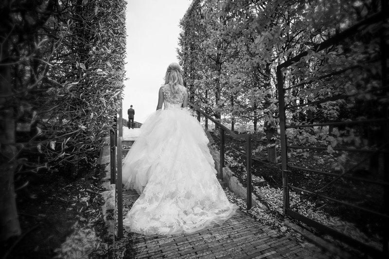 Black and white photo of bride in Vera Wang ball gown approaching groom for first look