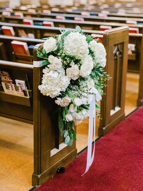 traditional church ceremony wood pews flower arrangments white hydrangea rose tulip ribbon greenery