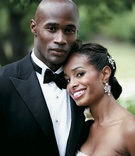 Model Christopher Collins in a black tuxedo with his bride in a Reem Acra gown
