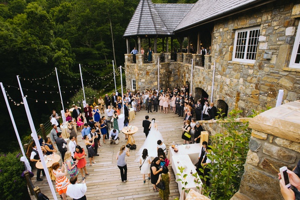 Guests standing on wood planks under string lights