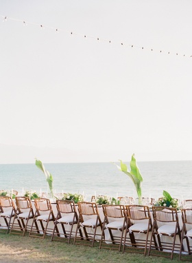 Wedding tablescape with ocean view string lights rattan wood chairs white cushions green palm leaf