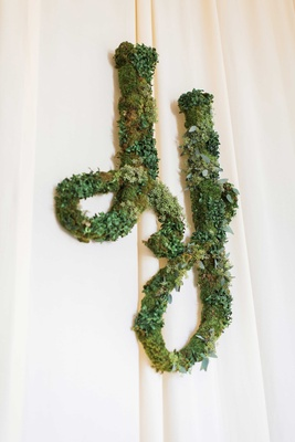 White drapery at wedding reception with verdant greenery installation of wedding monogram two J