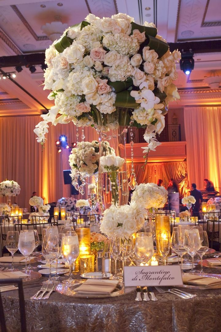 Wedding reception table with light tall and low floral arrangements and candles