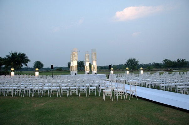 Outdoor white ceremony on grass lawn at hotel