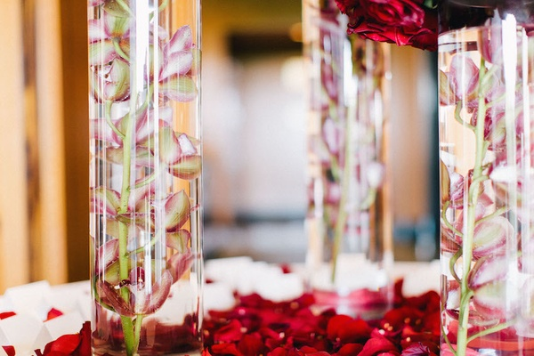 Wedding reception place card table with red flower petals and pink orchid stems in cylinder vases