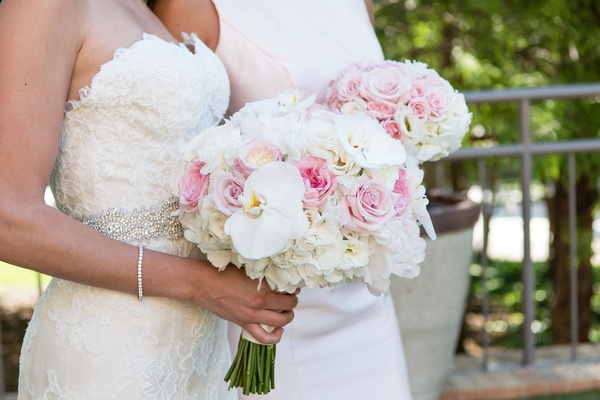 Bride in strapless lace wedding dress holding bouquet white orchid pink rose white hydrangea flowers