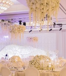 ivory floral fixtures over circular tables indian hindu wedding ghost chairs candles drapes