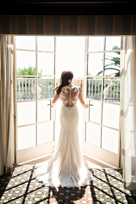 bride open double doors oceanside balcony overlooking wedding space illusion back sheath gown