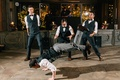 groom and groomsmen in tuxedos do a choreographed dance at reception to surprise bride with worm