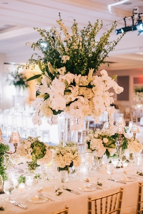 Wedding reception gold chairs white antique linens low centerpieces candelabra around tall flowers