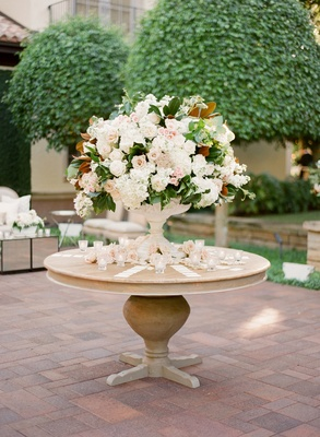 Garden wedding reception with a large arrangement of white and pink flowers in a white urn
