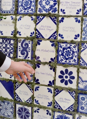 Wedding reception guest grabbing cocktail hour escort card blue white hand painted tile greenery