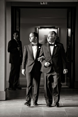 black and white photo of groom in ralph lauren black label walking with his father