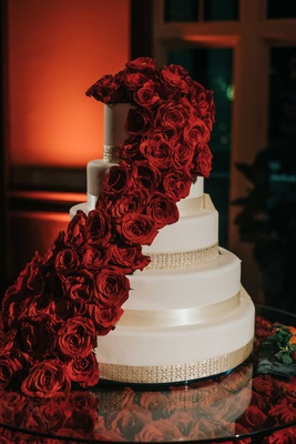 white five layer wedding cake with gold banding and crimson red roses cascading down layers
