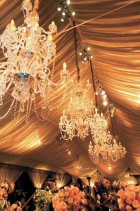 Chandeliers hanging from tented wedding reception