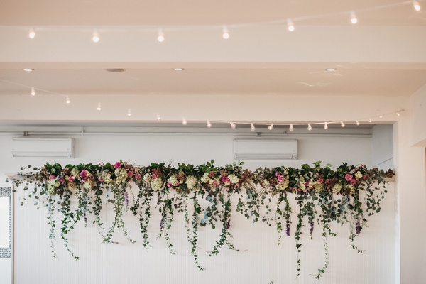 bistro lights overhead indoor reception and photo wall topped with florals and cascading ivy