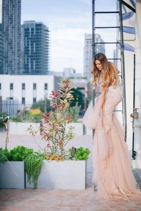 bride on fire escape staircase downtown los angeles wedding venue blush inbal dror wedding dress