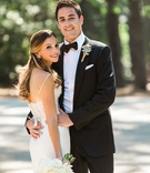 Bride in lace sleek wedding dress long hair earrings bouquet groom in bow tie and rustic boutonniere