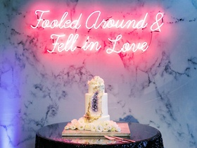 "geode wedding cake with neon sign above reading ""folled around & fell in love"""