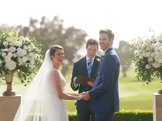 wedding ceremony bride in wedding dress veil groom in navy between white greenery flower arrangement