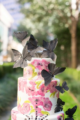 white cake with pink flower design and black jewels and black butterflies on top