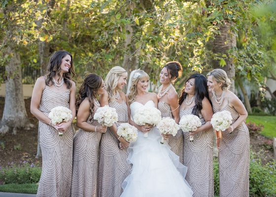 bride in layered, full ball gown, bridesmaids in adrianna papell taupe dresses with sequins
