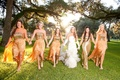 Bride in white gloves with bridesmaids in golden gowns
