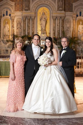 Bride and groom with mother and father in church