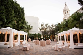 Courtyard outdoor cocktail hour with white cabana, green hedge bar, and cocktail tables