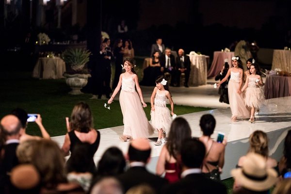 wedding ceremony night outdoor stage aisle flower girls in pink dresses holding hands