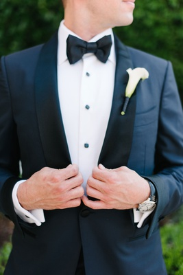 Groom in tuxedo with calla lily boutonniere and bow tie watch cuff links