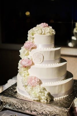 four-tiered wedding cake with ribbon detailing, cream roses pink peonies, initial seal with frosting