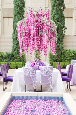 Garden wedding reception with floral tree of orchid garlands and tulip trunk, reflecting pool
