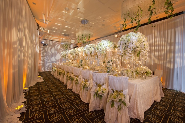 wedding styled shoot, lush king's table with orchids, patterned lighting on drapery walls