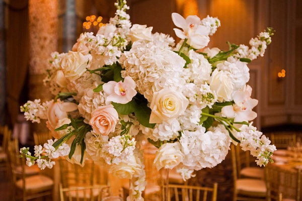 ivory and blush rose hydrangea and orchids floral arrangement with green leaves