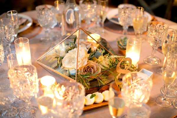 Rose gold copper geometric terrarium on table triangle with flowers surrounded by candles number