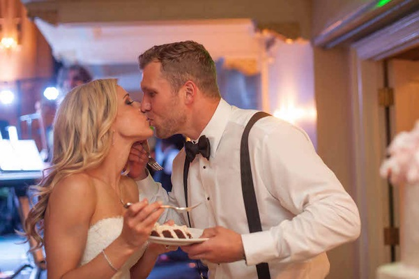 Brian Leonard, running back, in tuxedo shirt, suspenders, bow tie kisses bride in Isabelle Armstrong